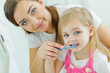 Mom and Daughter brushing their teeth - Pediatric Dentists